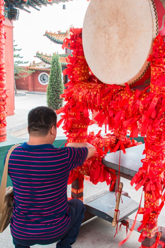 A worshipper tying prayer ribbon on the ceremonial drum