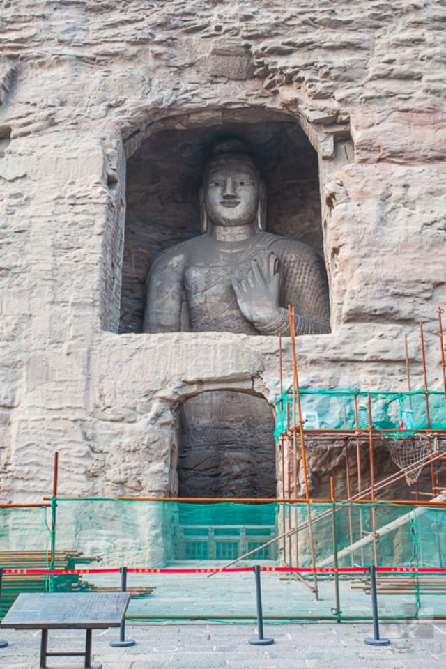 Giant stone Buddha scultpures in one of the caves at the Yungang Grottos under restorative repairs