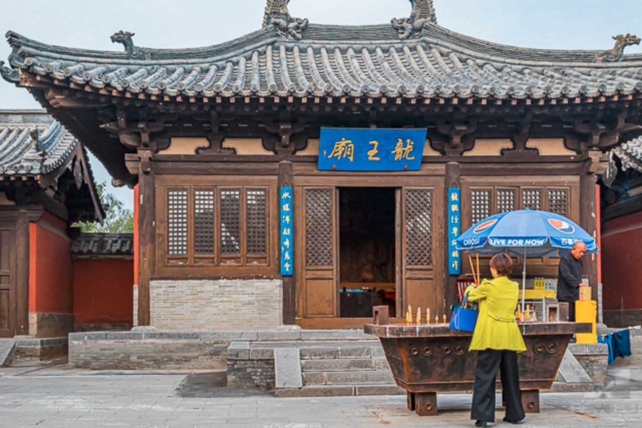 Entrance of a large wooden temple with a woman placing incense in the incense pot.