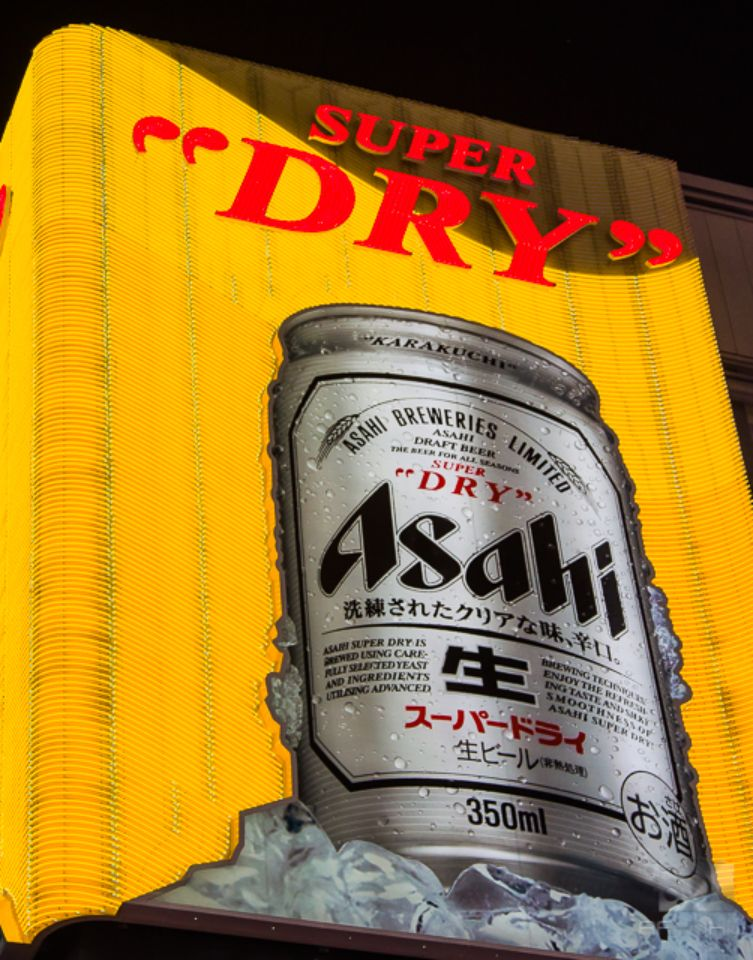 A giant can of Asahi beer with a bright yellow neon sign background in Dotonburi.